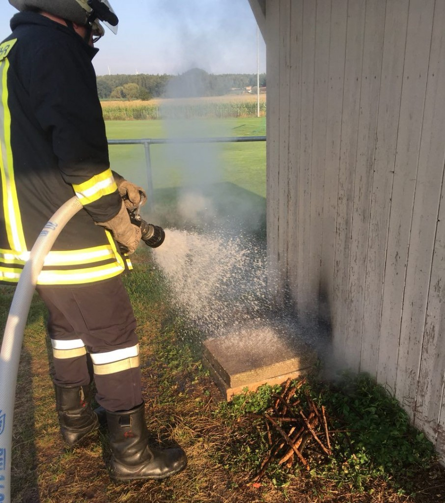 Feuerwehrmann löscht mit C-Rohr einen Kleinbrand